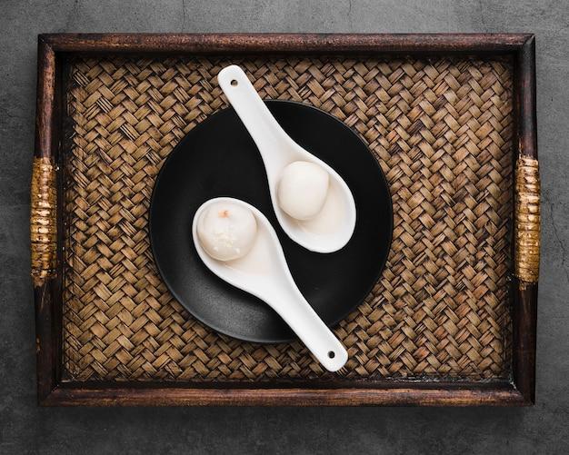 Vista superior de la bandeja con bolas de masa hervida en cucharas