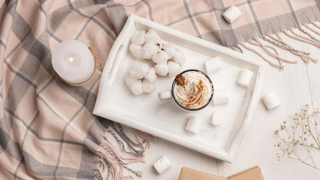 Vista superior de la bandeja con café con crema batida y vela