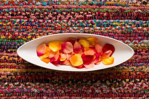 Vista superior de una bandeja de cerámica blanca con pétalos de diferentes colores sobre una alfombra colorida. adentro. concepto de deco tiempo de día.