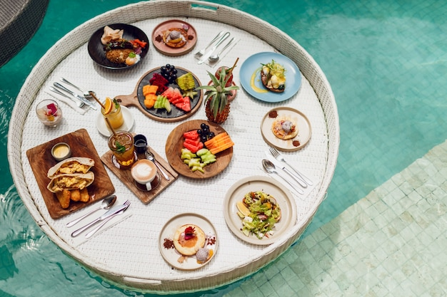 Vista superior de la bandeja de desayuno en la piscina, desayuno flotante en batidos de hotel de lujo y plato de frutas. dieta exótica de verano. estilo de vida de playa tropical. estilo balinés