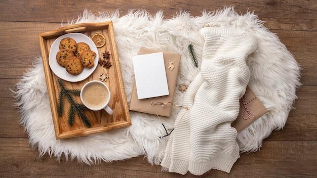 Vista superior de la bandeja con galletas y café junto al suéter