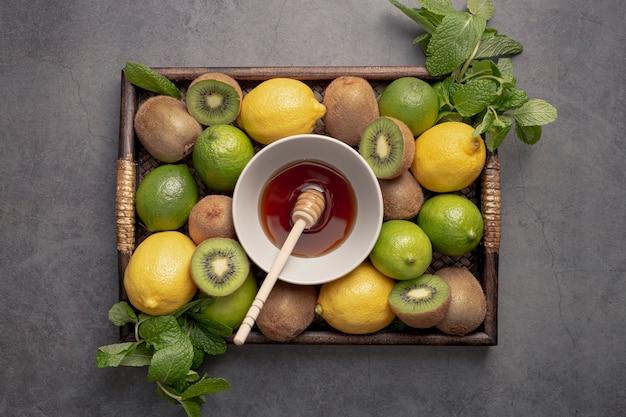 Vista superior de la bandeja con limones y kiwi con cucharón de miel