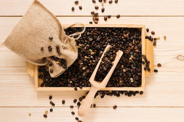 Vista superior de la bandeja de madera con granos de café.