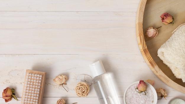 Vista superior bandeja de madera con productos cosméticos.
