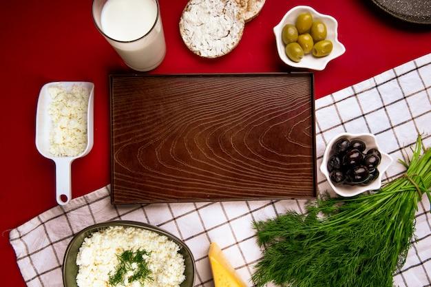 Vista superior de una bandeja de madera vacía y queso cottage en un tazón con aceitunas en escabeche eneldo y pasteles de arroz sobre tela escocesa en rojo