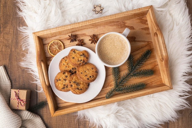 Vista superior de la bandeja con plato de galletas y taza de chocolate caliente