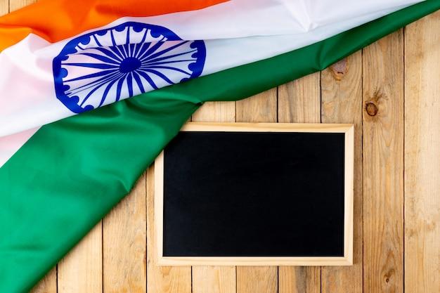 Vista superior de la bandera nacional de la india con pizarra sobre madera