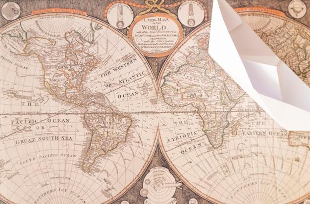 Vista superior barco de papel en el mapa del viejo mundo
