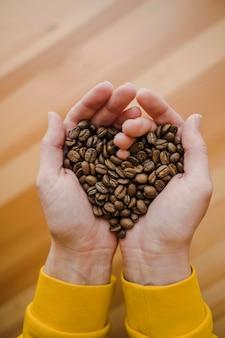 Vista superior de barista con granos de café en manos en forma de corazón