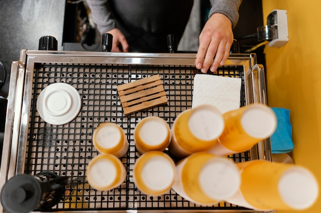 Vista superior del barista masculino en la máquina de café profesional