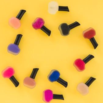 Vista superior de barniz de uñas de varios colores sobre fondo amarillo