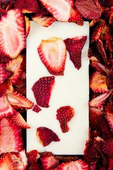 Vista superior de la barra de chocolate blanco sobre fondo de rodajas de fresa seca