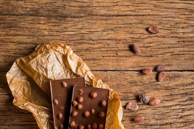 Vista superior barra de chocolate y granos de cacao en mesa de madera