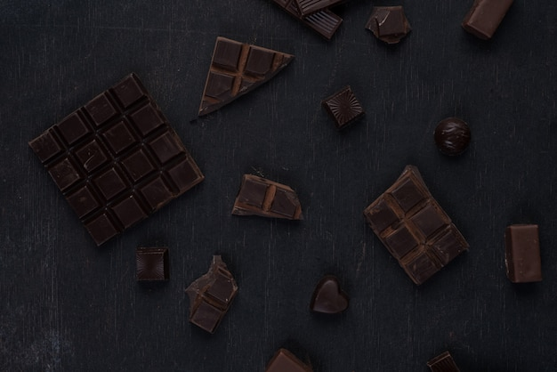 Vista superior de la barra de chocolate negro triturado con dulces