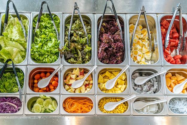Vista superior de la barra de ensaladas con varios tipos de verduras y frutas.