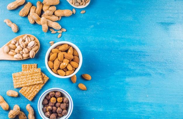 Vista superior de una barra saludable hecha con frutos secos y semillas sobre fondo azul pintado