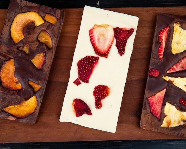 Vista superior de barras de chocolate blanco y oscuro con frutas en rodajas sobre una tabla de madera