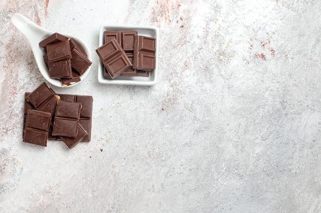 Vista superior de barras de chocolate en superficie blanca