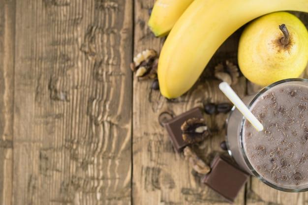 Vista superior de batido de chocolate con fruta en una mesa de madera.