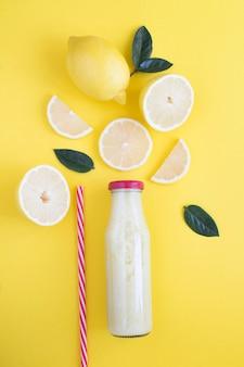 Vista superior de batido de limón en una botella de vidrio sobre fondo amarillo. de cerca.