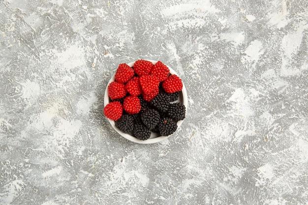 Vista superior de bayas frescas confita caramelos dulces dentro de la placa en la superficie blanca baya caramelo azúcar dulce pastel pastel cookie