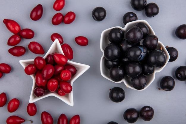 Vista superior de bayas frescas de cornel rojo en un recipiente en forma de estrella con uvas negras sobre un fondo gris