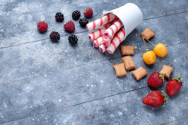 Vista superior de bayas y galletas con caramelos de palo rosa en un escritorio brillante, galleta de frutas y bayas