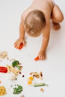 Vista superior del bebé eligiendo qué comer solo