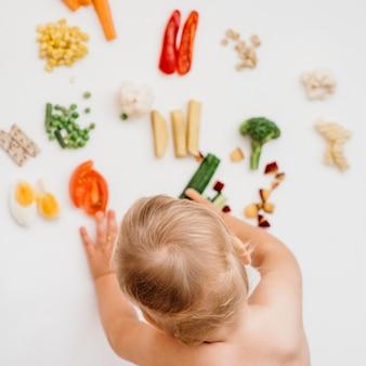 Vista superior del bebé eligiendo qué comer