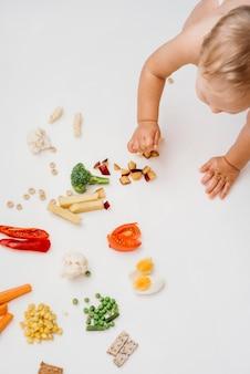 Vista superior del bebé rubio eligiendo qué comer