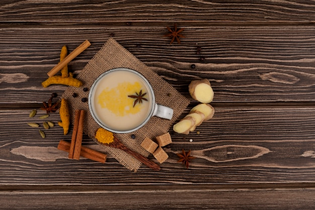 Vista superior de la bebida tradicional india masala chai, té con leche y especias en madera