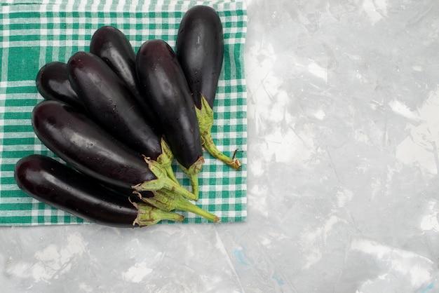 Vista superior berenjenas negras frescas maduras frescas en el brillante escritorio comida vegetal plato de comida cruda
