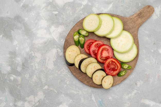 Vista superior, berenjenas en rodajas, calabazas y tomates en el brillante escritorio plato de comida vegetal crudo