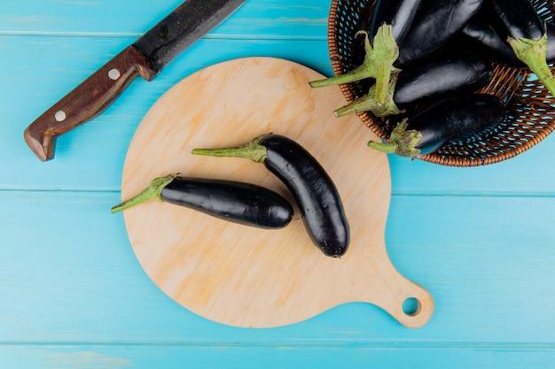 Vista superior de berenjenas en tabla de cortar con otras en cesta y cuchillo sobre fondo azul.