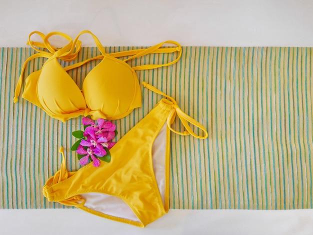 Vista superior de bikini amarillo con orquídea púrpura en tela abstracta