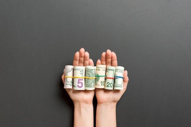 Vista superior de billetes de dólar enrollados en tubos en palmas femeninas sobre fondo negro