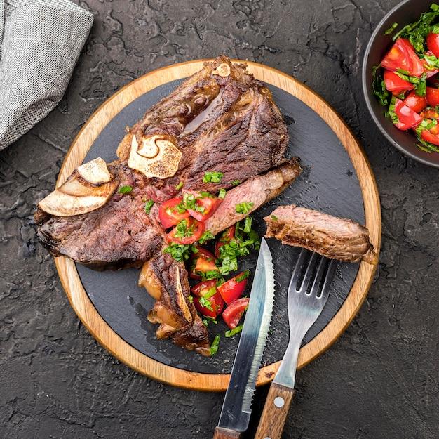 Vista superior de bistec con cubiertos y ensalada