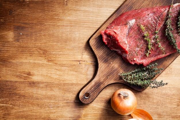 Vista superior del bistec en la tabla de cortar de madera junto a la cebolla blanca. carne para cocinar. romero verde.
