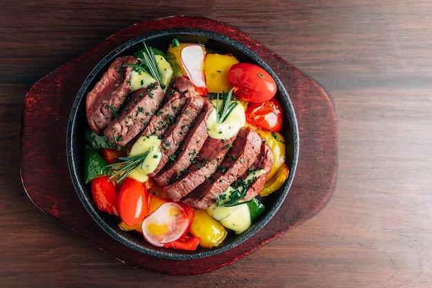 Vista superior de un bistec de ternera poco común servido en un plato caliente con tomate, pimiento, rábano y romero.