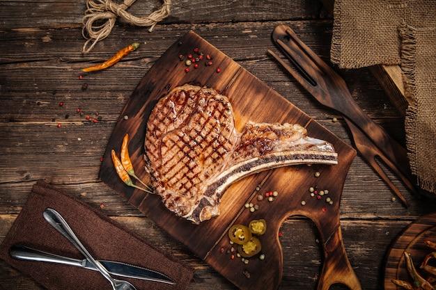 Vista superior de bistec tomahawk jugoso a la parrilla en la tabla de madera decorada