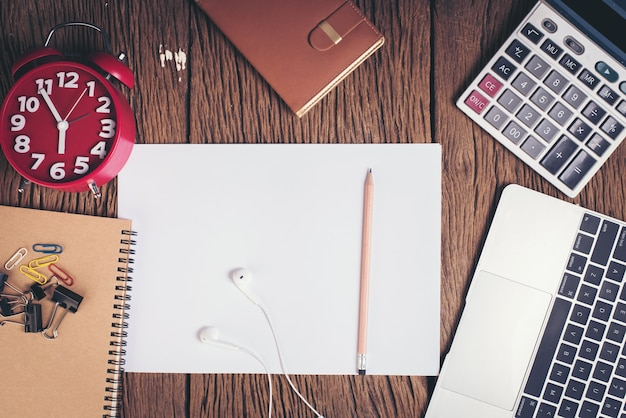 Vista superior en blanco papel blanco en el espacio de trabajo de escritorio de madera