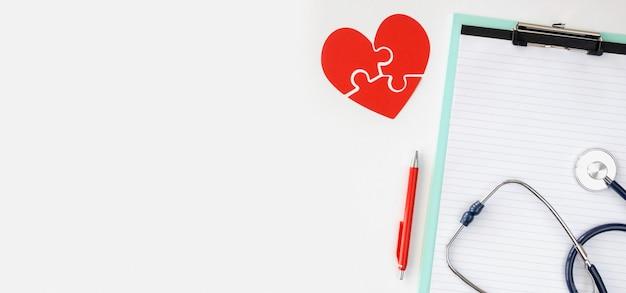 Vista superior del bloc de notas con corazón de papel de rompecabezas y espacio de copia