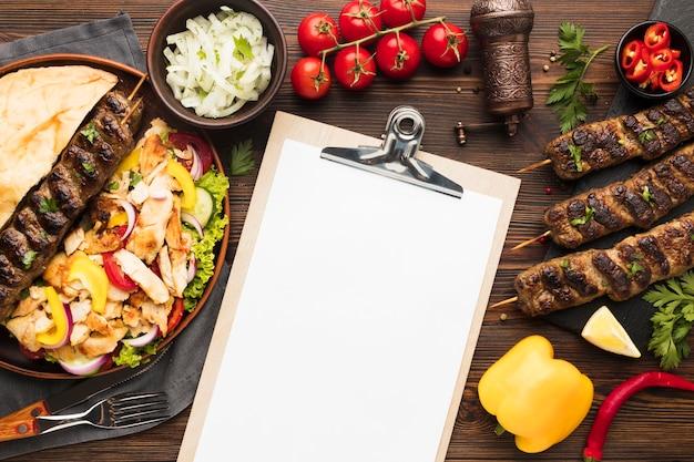 Vista superior del bloc de notas con deliciosos kebabs y verduras