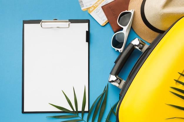 Vista superior del bloc de notas con equipaje y elementos esenciales de viaje