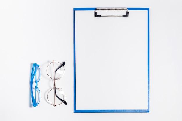 Vista superior del bloc de notas con gafas