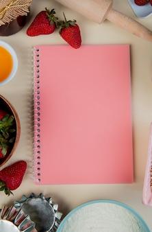 Vista superior del bloc de notas con harina de mantequilla de fresas alrededor en una superficie blanca con espacio de copia