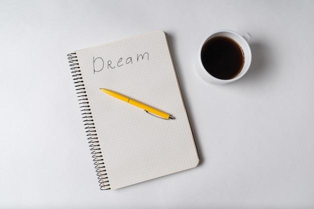 Vista superior del bloc de notas con la inscripción sueño. pluma y taza de café. nota motivacional