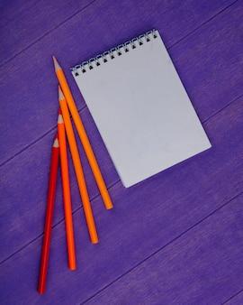 Vista superior del bloc de notas y lápices de colores sobre fondo morado con espacio de copia