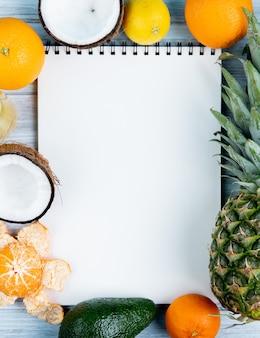Vista superior del bloc de notas con naranja, coco, mandarina, aguacate, piña, limón alrededor sobre fondo de madera con espacio de copia