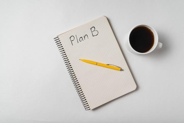 Vista superior del bloc de notas con las palabras plan b y una taza de café. ideas de planes de respaldo